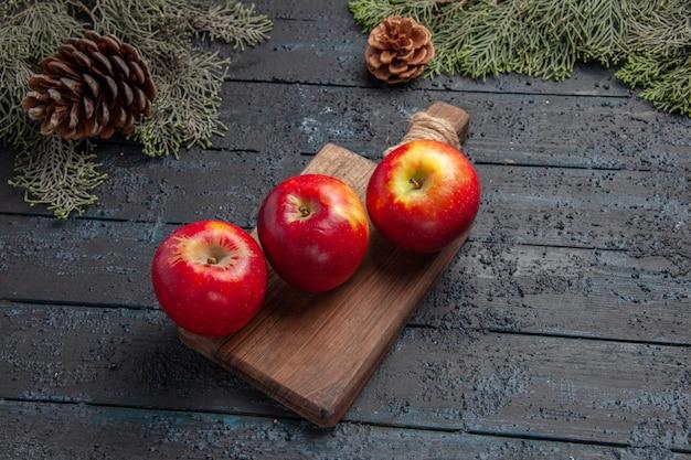 Vista superior das frutas na mesa três maçãs na tábua de madeira entre galhos com cones