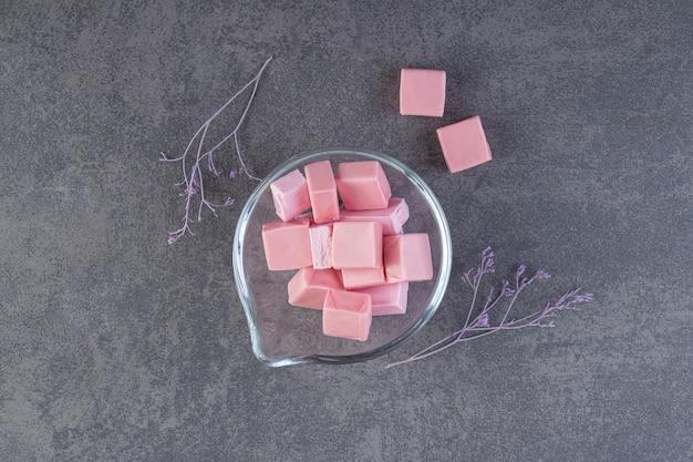Vista superior das gengivas rosa em uma tigela de vidro sobre a superfície cinza.