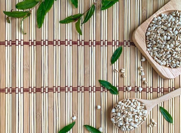 Vista superior das lágrimas de trabalho ou painço em uma bandeja e uma colher de pau. o fundo é um tapete de madeira decorado com folhas de romã