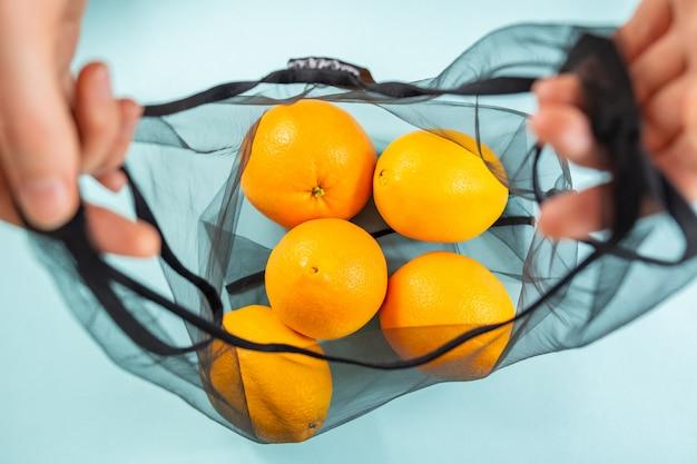 Vista superior das laranjas em uma sacola reutilizável.