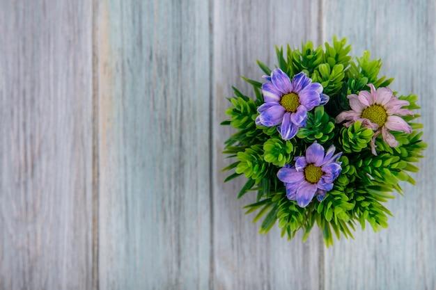 Vista superior das lindas flores coloridas da margarida em um fundo cinza de madeira com espaço de cópia
