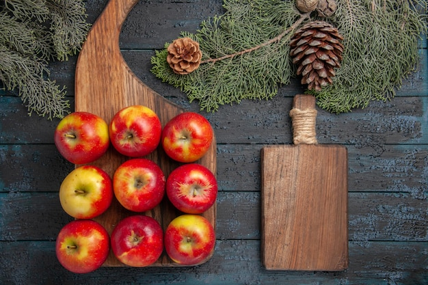 Vista superior das maçãs a bordo de nove maçãs amarelo-avermelhadas na superfície cinza e uma tábua de cortar entre os galhos das árvores