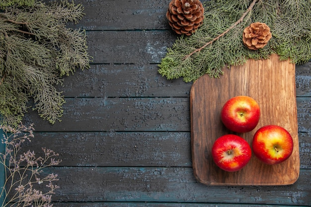 Vista superior das maçãs a bordo de três maçãs amarelo-avermelhadas na tábua de corte marrom sob os banchos das árvores com cones no lado direito da mesa