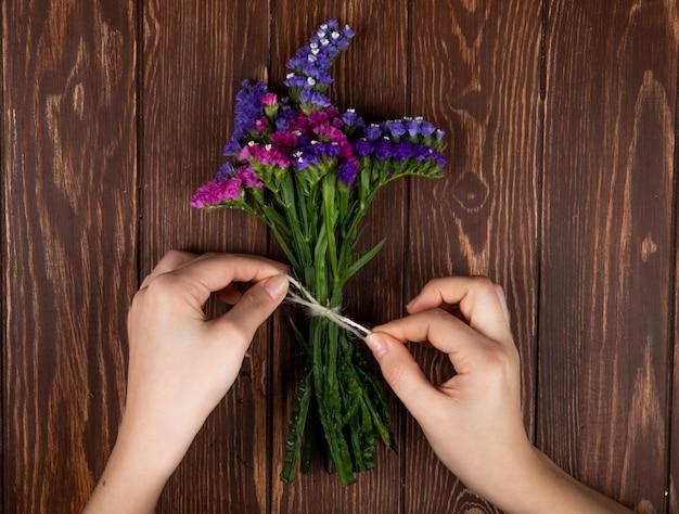 Vista superior das mãos, amarrando com uma corda, um buquê de flores de statice limonium cor de rosa e roxo sobre fundo rústico de madeira