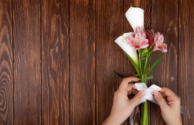Vista superior das mãos, amarrando com uma fita, um buquê de flores cor de rosa e branco alstroemeria e lírios em fundo de madeira com espaço de cópia