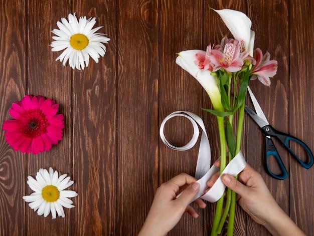 Vista superior das mãos, amarrando com uma fita, um buquê de flores cor de rosa e branco alstroemeria e lírios em fundo de madeira