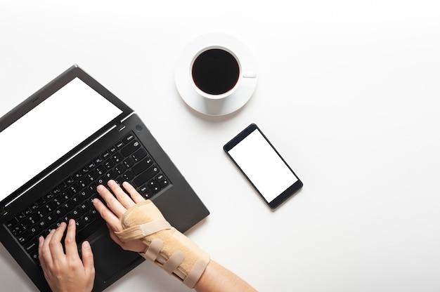 Vista superior das mãos com dor no pulso de usar o computador