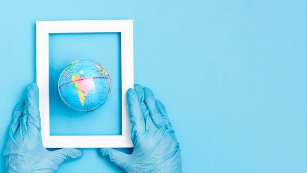 Vista superior das mãos com luvas cirúrgicas, segurando o quadro sobre o globo da terra com espaço de cópia