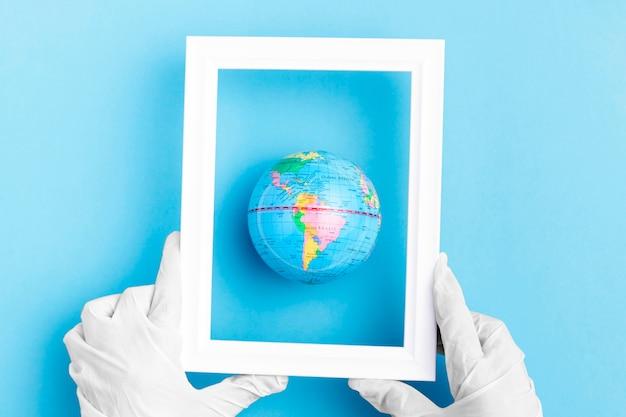 Vista superior das mãos com luvas cirúrgicas, segurando o quadro sobre o globo da terra