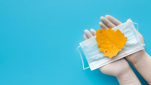 Vista superior das mãos com luvas segurando máscara médica com folha de outono