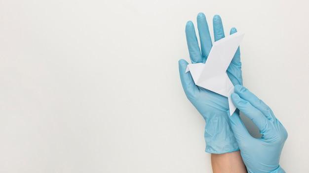 Vista superior das mãos com luvas segurando uma pomba com espaço de cópia
