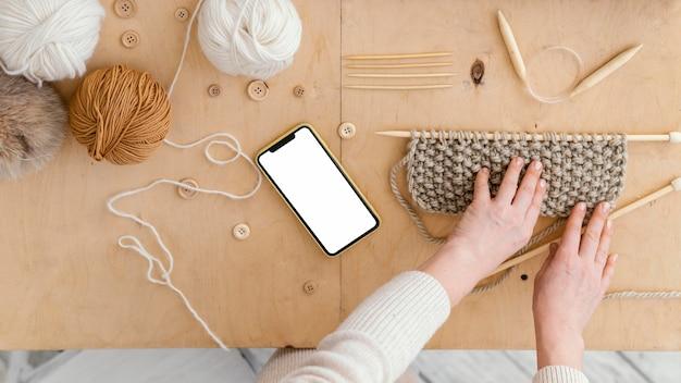 Vista superior das mãos com mesa de tricô