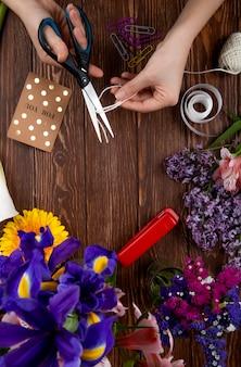 Vista superior das mãos com uma tesoura cortando clipes de papel cartão postal de corda e um buquê de flores de íris roxo em fundo de madeira