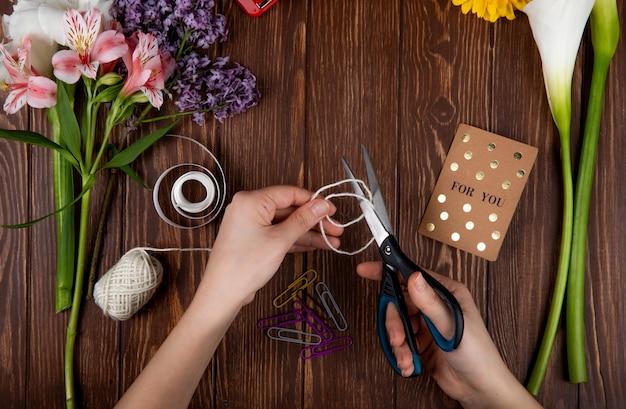 Vista superior das mãos com uma tesoura cortando uma corda clipes de papel cartão postal e um buquê de flores de alstroemeria rosa com lilás sobre fundo de madeira