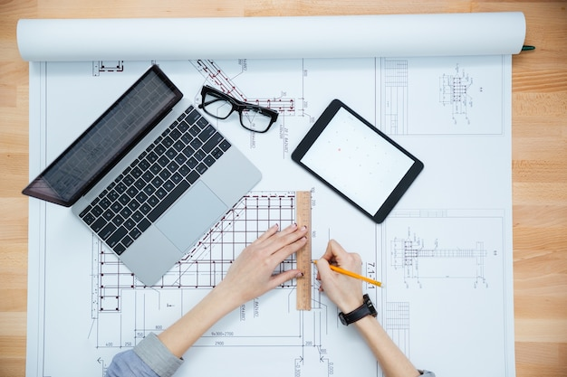 Vista superior das mãos da arquiteta, desenhando a planta e usando laptop e tablet
