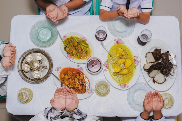Vista superior das mãos da família orando antes de comer com o menu servido na mesa durante o eid mubarak