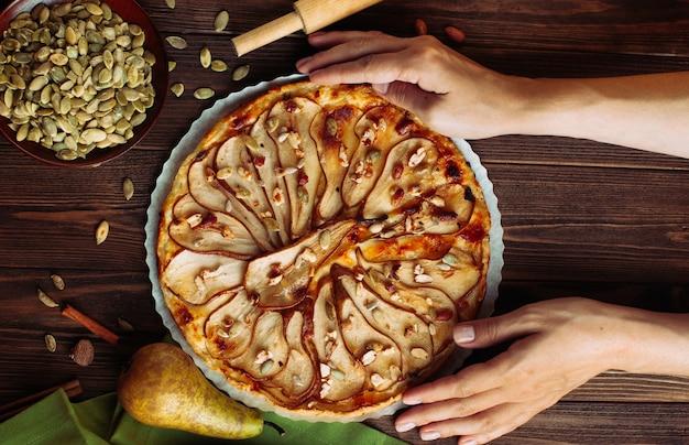 Vista superior das mãos da mulher segurando a torta de pêra em fundo de madeira rústica