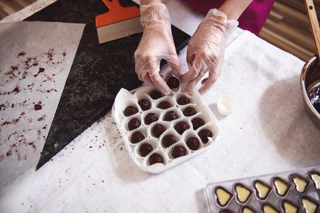 Vista superior das mãos de chocolatier em luvas brancas transparentes embalando trufas de chocolate em uma caixa próxima a moldes com recheio de caramelo salgado