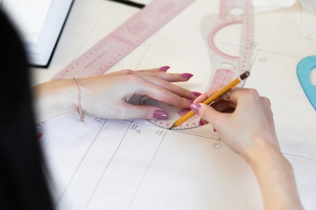Vista superior das mãos de costureira, fazendo um padrão em um papel vegetal branco.