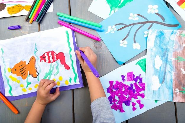 Vista superior das mãos de criança com imagens de pintura a lápis em papel