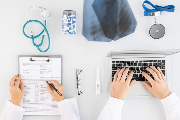 Vista superior das mãos de dois jovens médicos em jalecos brancos fazendo anotações médicas e digitando em um laptop cercado por uma variedade de suprimentos