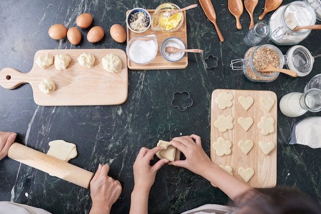 Vista superior das mãos de duas pessoas juntos a cozinhar biscoitos caseiros