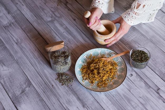 Vista superior das mãos de mulher com ingredientes na mesa, pilão de madeira, açafrão amarelo, lavanda e folhas naturais verdes. de perto, durante o dia