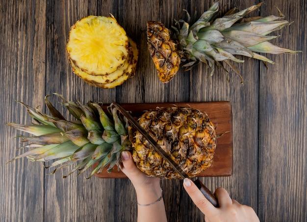 Vista superior das mãos de mulher cortando abacaxi com faca na tábua com abacaxi fatiado na mesa de madeira