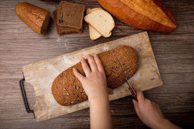 Vista superior das mãos de mulher cortando pão de sanduíche na tábua e outros pães em fundo de madeira
