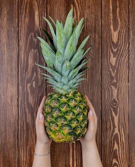 Vista superior das mãos de mulher segurando abacaxi na mesa de madeira