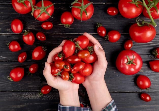 Vista superior das mãos de mulher segurando tomates com outros na mesa de madeira