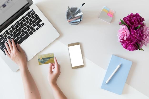 Vista superior das mãos de mulher segurando um cartão de crédito, conceito de compras on-line, espaço de trabalho com computador portátil, telefone celular, flores e notebook, configuração plana.