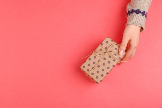 Vista superior das mãos de mulher segurando uma caixa de presente rosa