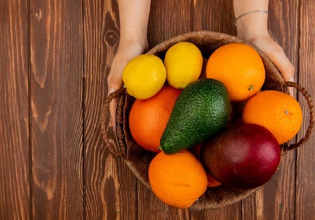 Vista superior das mãos de mulher segurando uma cesta cheia de frutas cítricas como laranja abacate manga limão na mesa de madeira com espaço de cópia