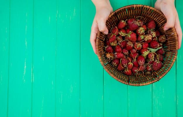Vista superior das mãos de mulher segurando uma cesta com morangos no lado direito e mesa verde
