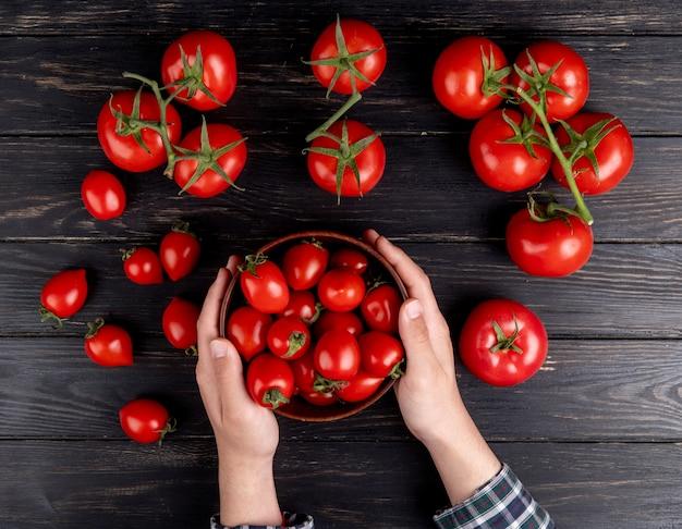 Vista superior das mãos de mulher segurando uma tigela de tomate com outros na mesa de madeira