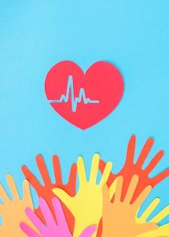 Vista superior das mãos de papel com coração e batimentos cardíacos