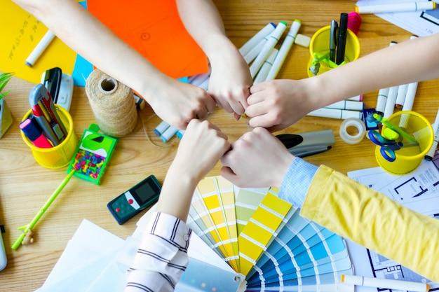 Vista superior das mãos de pessoas de negócios, juntando os punhos sobre a mesa no escritório criativo. arquitetos e designers de interiores na mesa com amostras de cores, layouts de sala, material de escritório. conceito trabalho em equipe