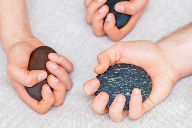 Vista superior das mãos de três massoterapeutas segurando pedras de massagem
