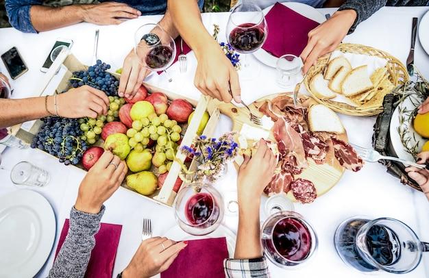Vista superior das mãos de um amigo comendo comida e vinho na festa de churrasco no jardim