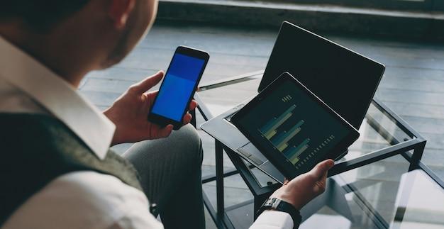 Vista superior das mãos de um homem de negócios usando um smartphone e um tablet no escritório enquanto trabalhava.
