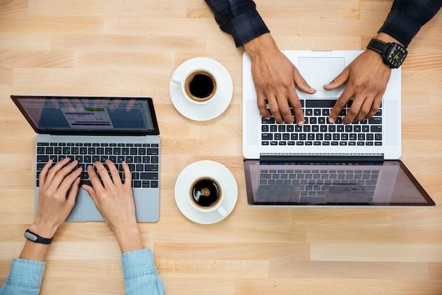 Vista superior das mãos de um homem e uma mulher trabalhando com dois laptops e bebendo café na mesa de madeira
