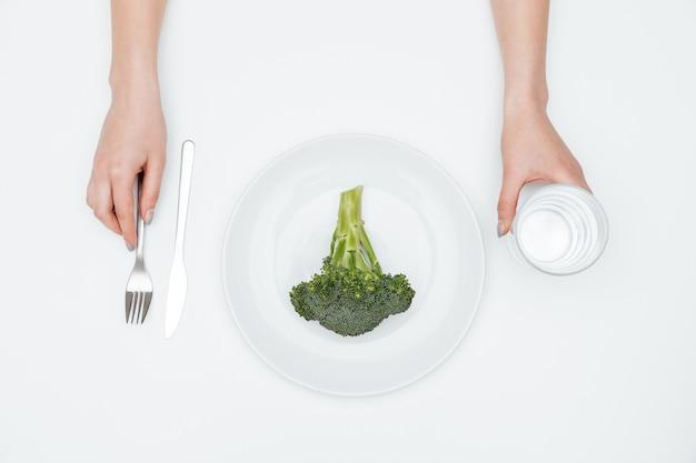 Vista superior das mãos de uma jovem bebendo água e comendo brócolis