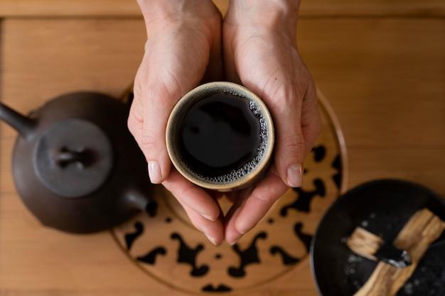 Vista superior das mãos de uma mulher com uma xícara de chá e uma chaleira