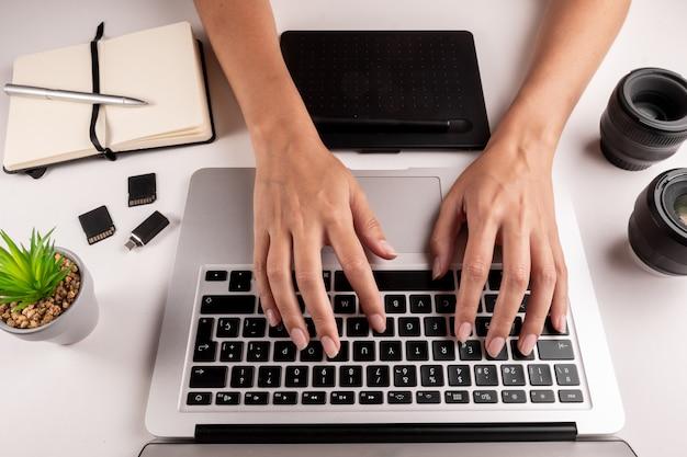 Vista superior das mãos de uma mulher digitando em um teclado de computador