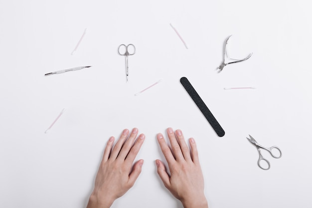 Vista superior das mãos de uma mulher e ferramentas para manicure