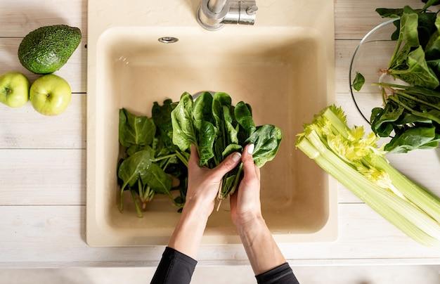 Vista superior das mãos de uma mulher lavando espinafre na pia da cozinha