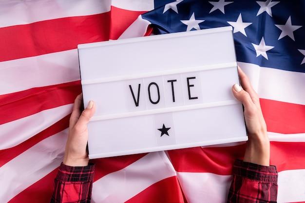 Vista superior das mãos de uma mulher segurando uma mesa de luz com a palavra vote na bandeira americana plano de fundo leigo
