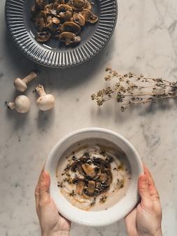 Vista superior das mãos de uma mulher segurando uma tigela de sopa de cogumelos