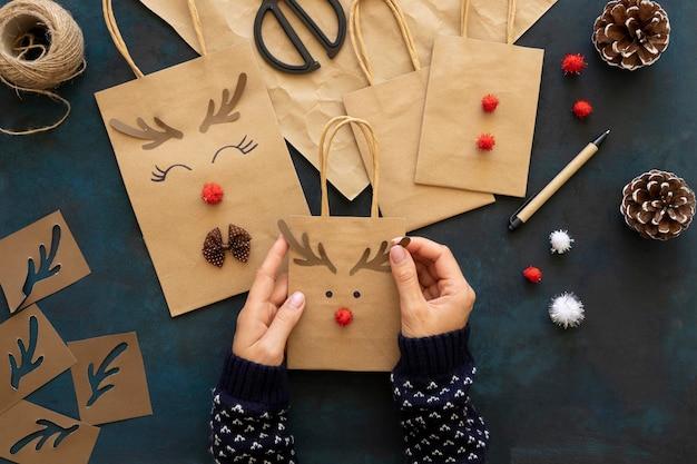 Vista superior das mãos decorando sacolas de papel de natal
